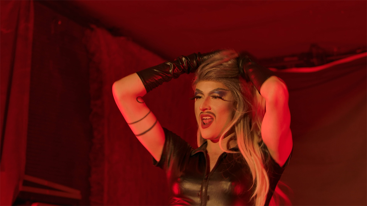 A drag queen on stage in a leather outfit rubs her hands through her hair