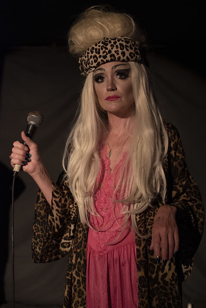 A woman dressed in pink with a blonde wig stands on stage with a microphone